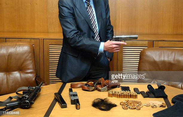 A police officer holds the automatic pistol as the submachine gun the bulletproof vest amunitions a false beard and moustache are displayed on the...