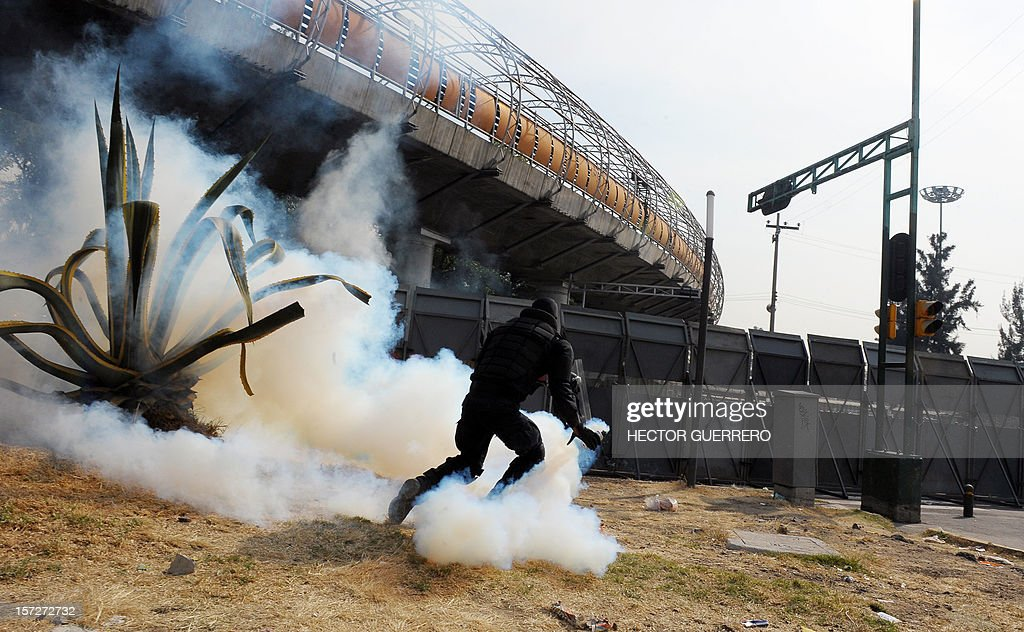 A police officer hurls a tear gas canister during clashes with rioters outside of the Congress before the inauguration ceremony of incoming Mexican President Enrique Pena Nieto on December 1, 2012, in Mexico City. Pena Nieto was sworn in as president of Mexico on Saturday following protests by leftist lawmakers inside the congress and clashes between demonstrators and police outside. AFP PHOTO/Hector Guerrero
