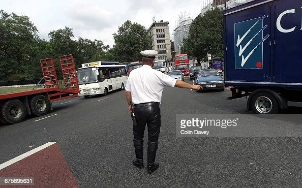 A police officer in leather trousers directs traffic during a fuel protest on Park Lane London 13th September 2000