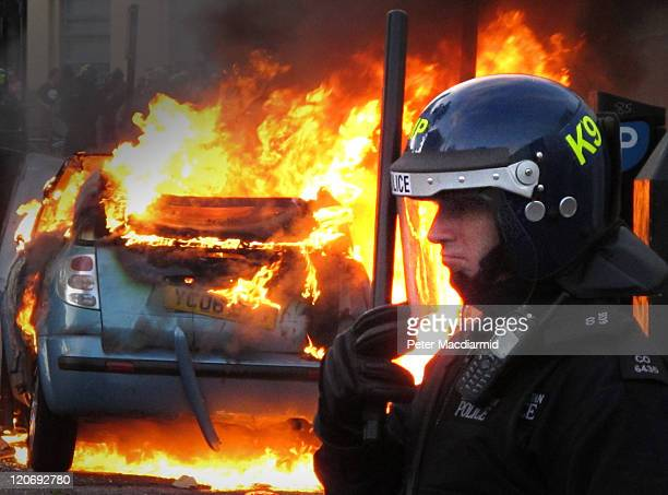 A police officer in riot gear stands near a burning car in Hackney on August 8 2011 in London England Pockets of rioting and looting continues to...