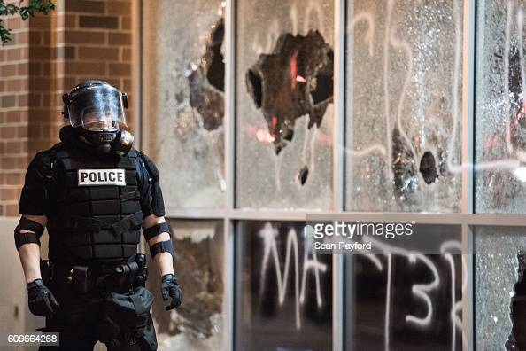 A police officer in riot gear stands near a damaged storefront September 21 2016 in downtown Charlotte NC Protests in Charlotte began on Tuesday in...