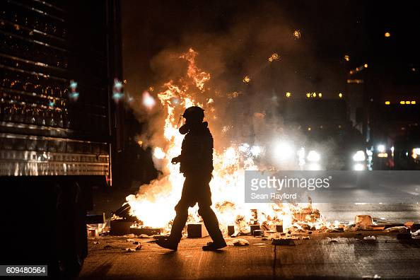 A police officer in riot gear walks past a fire on the I85 during protests in the early hours of September 21 2016 in Charlotte North Carolina The...