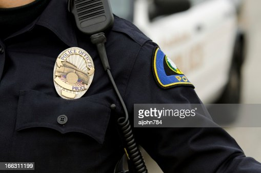 A police officer in uniform with a badge : Stock Photo