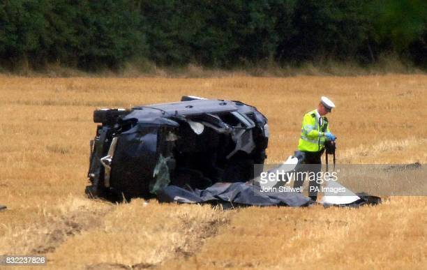 A police officer inspecting a people carrier lying on its side in a field close to junction 29 of the M25 motorway after the car crashed earlier this...