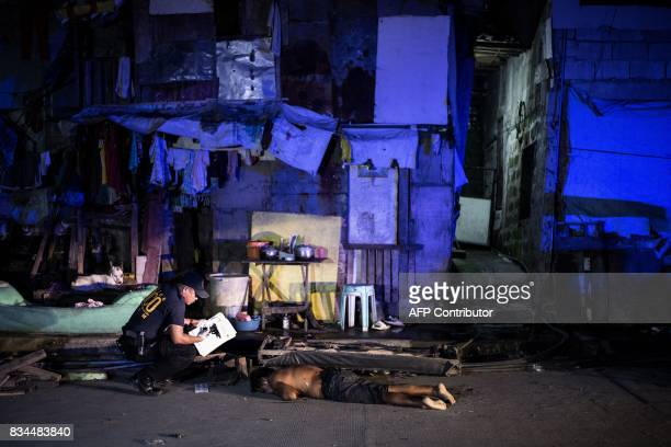 A police officer investigates the dead body of an alleged drug dealer killed during a police antidrug operation in Manila on August 18 2017 It's just...