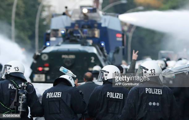 A police officer is hit by a bottle as riot police use water cannon during the 'Welcome to Hell' rally against the G20 summit in Hamburg northern...