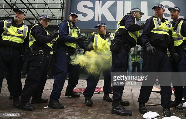 A police officer is hit by a smoke flare thrown by protesters outside the Department for Business Innovation and Skills during the annual...