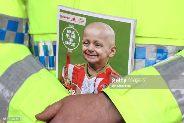 A police officer is seen holding the match day programme displaying a image of Bradley Lowery outside the stadium prior to the Premier League match...