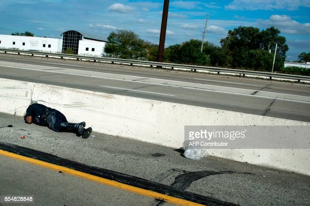 A police officer is seen on the road after falling from a motorcycle while sorting a motorcade with US President Donald Trump to Indianapolis...