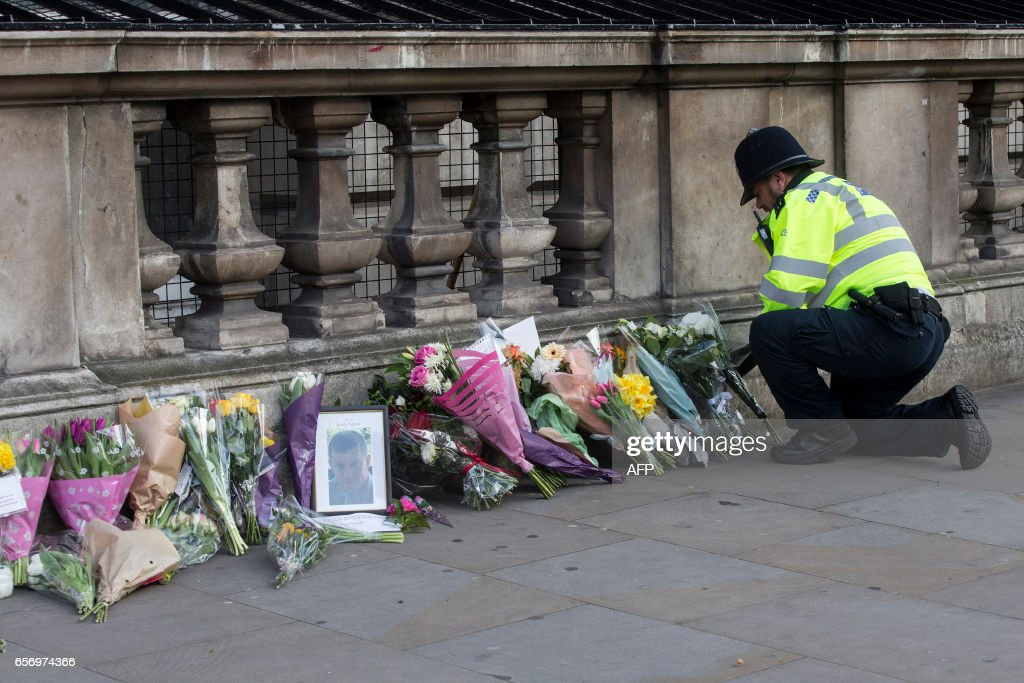 TOPSHOT - A police officer is seen with flowers in honour of the victims of the March 22 terror attack on Whitehall in central London on March 23, 2017. Britain's parliament reopened on Thursday with a minute's silence in a gesture of defiance a day after an attacker sowed terror in the heart of Westminster, killing three people before being shot dead. Sombre-looking lawmakers in a packed House of Commons chamber bowed their heads and police officers also marked the silence standing outside the headquarters of London's Metropolitan Police nearby. PHOTO / Joel Ford