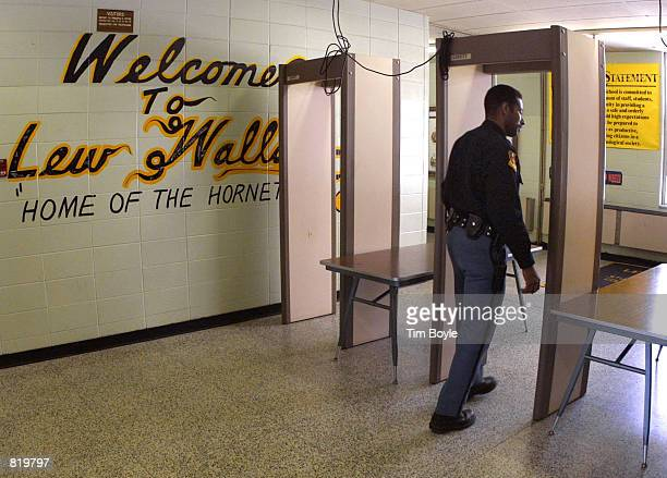 Police Officer Jeff Tatum passes through a metal detector at Lew Wallace High School March 30 2001 in Gary IN after 16yearold sophomore Neal Boyd Jr...