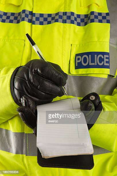 Police officer jotting down details in his notepad