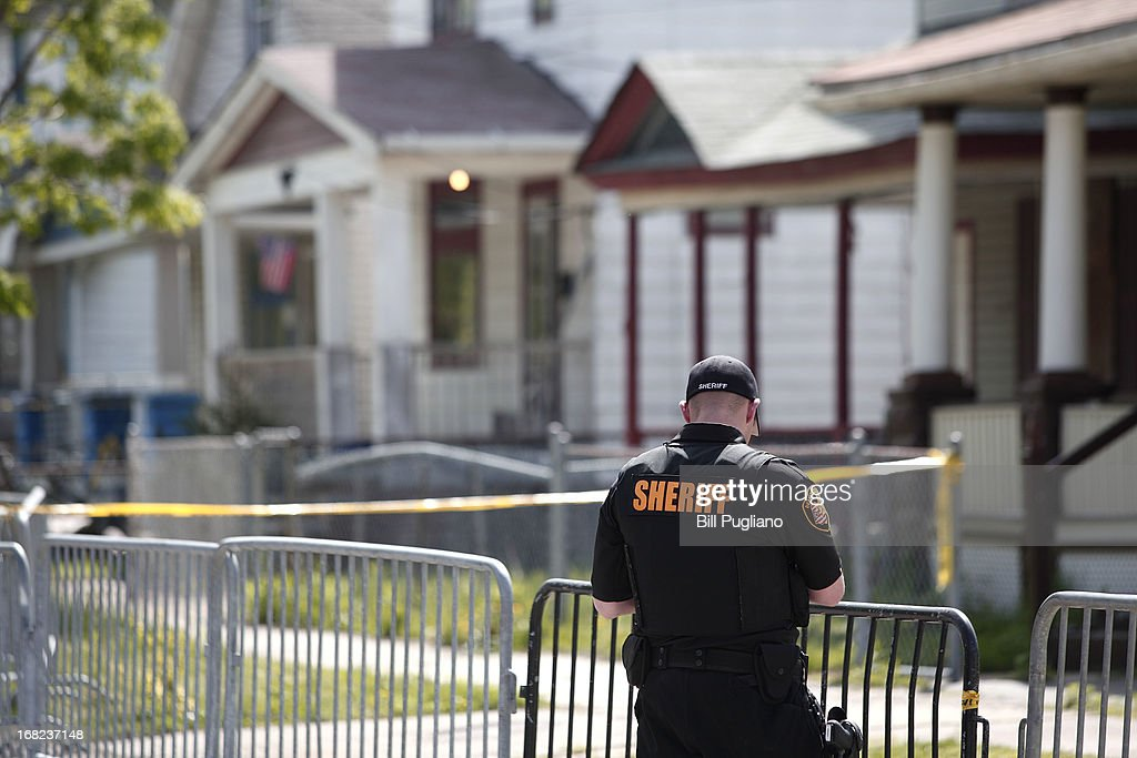 A police officer keeps the public away from the house where three women, who disappeared as teens about a decade ago, were found alive May 7, 2013 in Cleveland, Ohio. Amanda Berry, who went missing in 2003, Gina DeJesus, who went missing in 2004, and Michelle Knight, who went missing in 2002, managed to escape their captors on May 6, 2013. Three suspects, all brothers, were taken into custody.