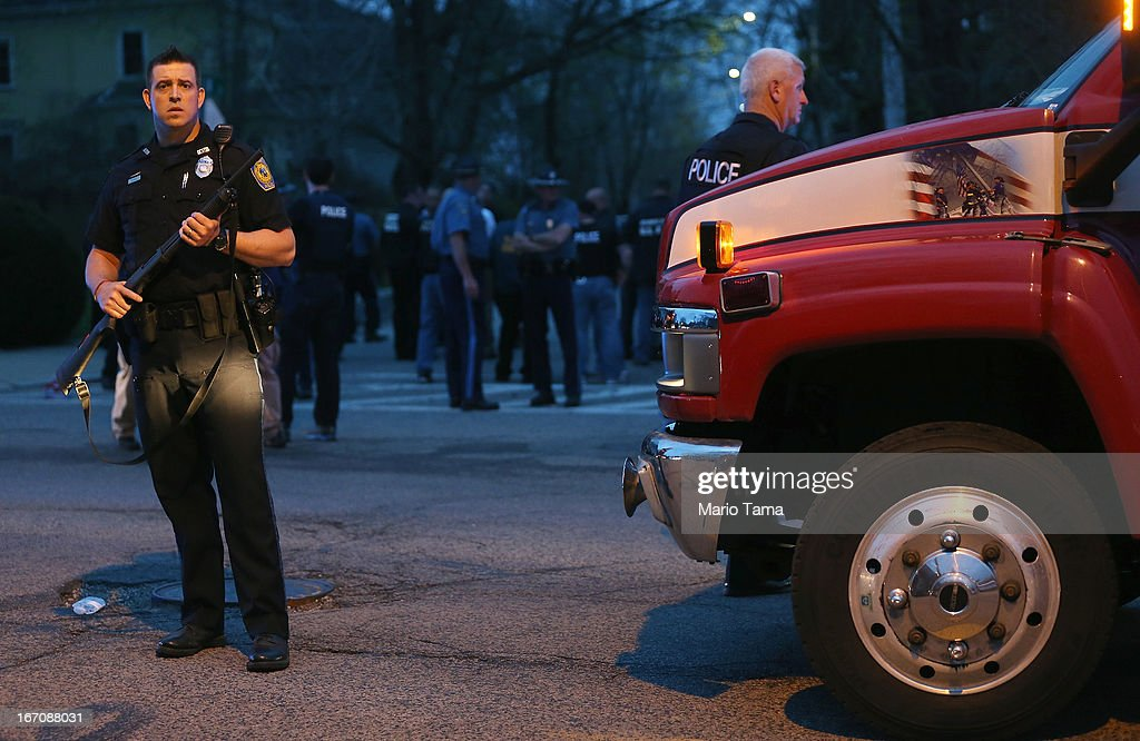 A police officer keeps watch after responding to a reported shooting next to a small 9/11 tribute painted on a truck on April 19, 2013 in Watertown, Massachusetts. After a car chase and shoot out with police, one suspect in the Boston Marathon bombing, Tamerlan Tsarnaev, 26, was shot and killed by police early morning April 19, and a manhunt is underway for his brother and second suspect, 19-year-old suspect Dzhokhar A. Tsarnaev. The two men, reportedly Chechen of origin, are suspects in the bombings at the Boston Marathon on April 15, that killed three people and wounded at least 170.