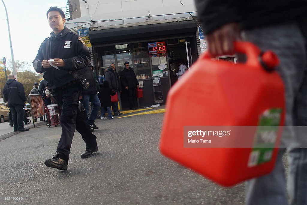 A police officer keeps watch as people wait on line to purchase gasoline on East Houston Street in Lower Manhattan following Superstorm Sandy on November 4, 2012 in New York City. With the death toll currently over 100 and millions of homes and businesses without power, the U.S. East Coast is attempting to recover from the effects of floods, fires and power outages brought on by Superstorm Sandy.