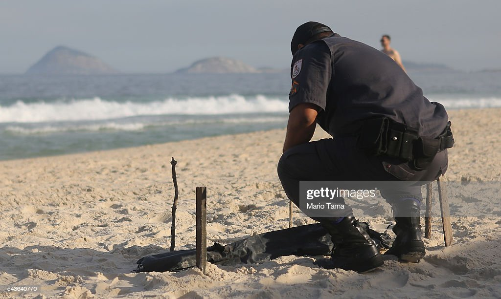A police officer kneels over a body part, covered in a plastic bag, which was discovered on Copacabana Beach near the Olympic beach volleyball venue on June 29, 2016 in Rio de Janeiro, Brazil. Parts of a mutilated body were discovered on the sands of the beach while it remains unknown how the person died. The Rio 2016 Olympic Games begin August 5 amidst an economic crisis in the country.