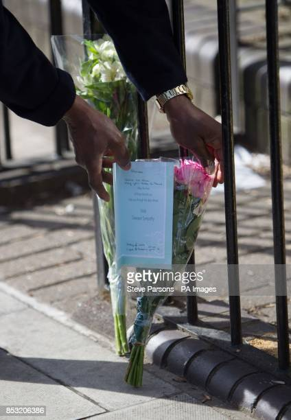 A police officer lays flowers handed to him at the scene in Eastway Hackney east London where a teenage girl named as Shereka Marsh died after a...
