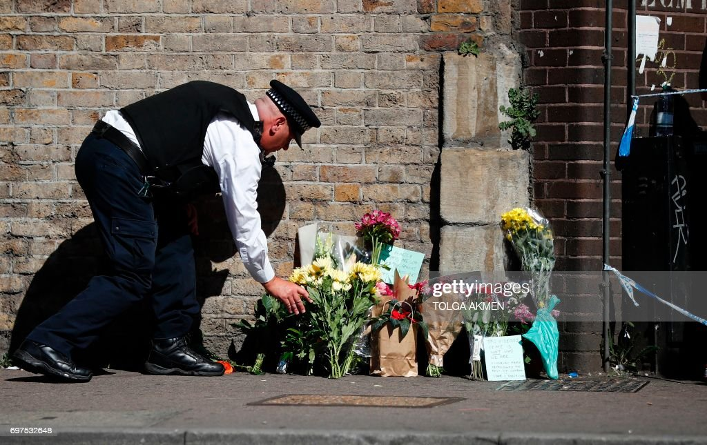 A police officer lays flowers inside a police cordon near the scene in Finsbury Park area of north London after a vehicle was driven into pedestrians, on June 19, 2017. Ten people were injured when a van drove into a crowd of Muslim worshippers near a mosque in London in the early hours of Monday, and a man who had been taken ill before the attack died at the scene. / AFP PHOTO / Tolga AKMEN