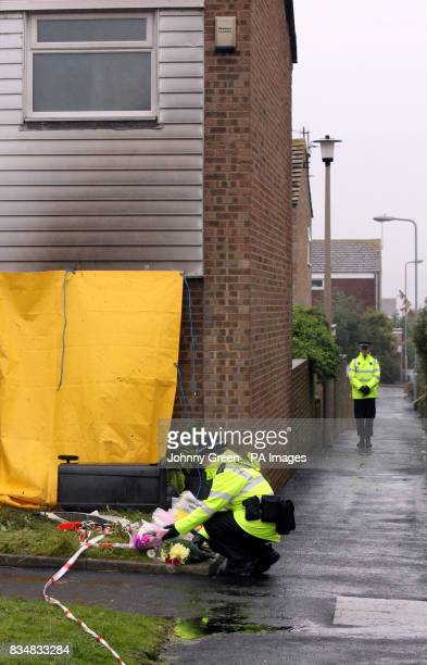 A police officer lays flowers outside a house in Milfoil Drive Eastbourne East Sussex where two children were found dead following a house fire there...