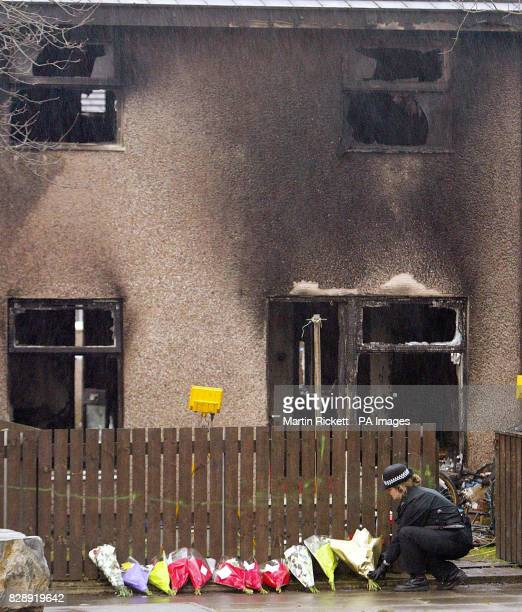 A police officer lays flowers outside the house in Will Griffiths Walk Beswick Manchester where a fire killed three young children and an adult The...
