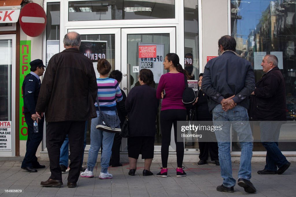A police officer, left, talks with customers as they queue outside a branch of Cyprus Popular Bank Pcl, also known as Laiki Bank, in Nicosia, Cyprus, on Friday, March 29, 2013. Cypriots face a second day of bank controls over their use of the euro as officials in Europe urged the country to move quickly to lift the restrictions, the first time they have been imposed on the common currency. Photographer: Simon Dawson/Bloomberg via Getty Images