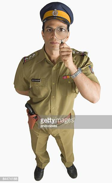 Police officer looking through a magnifying glass