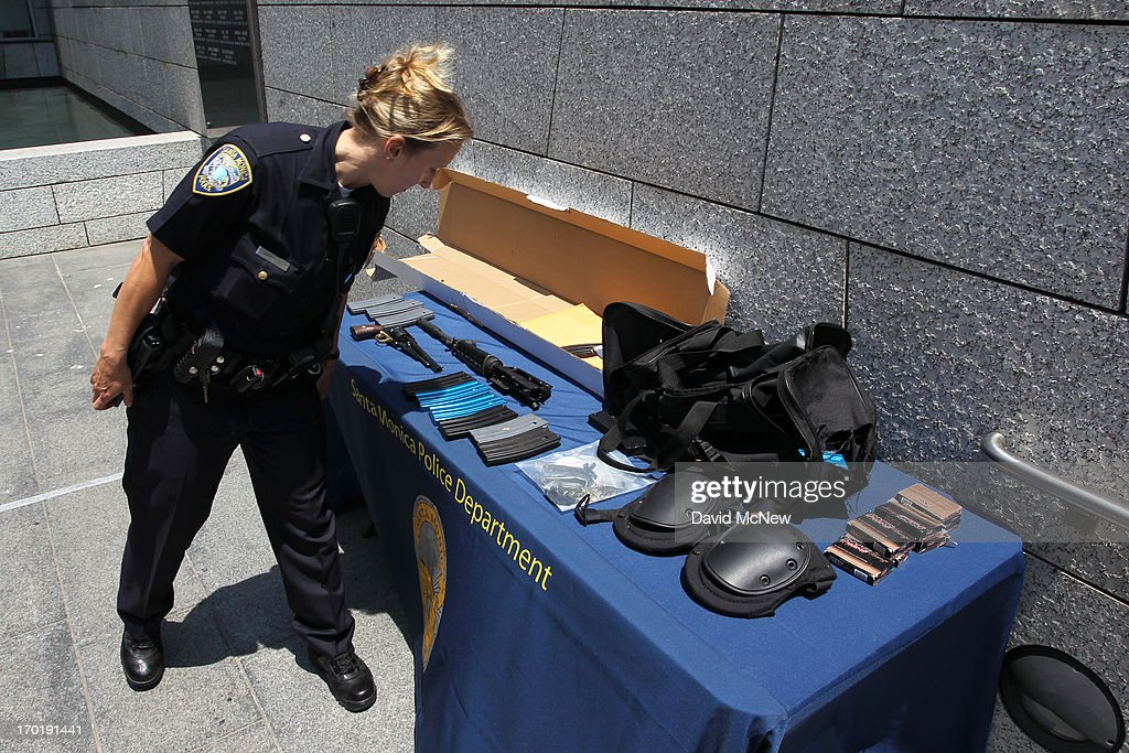 A police officer looks at evidence allegedly dropped by a gunman during a mass shooting spree that ended at Santa Monica College where he was shot dead by police on June 8, 2013 in Santa Monica, California. The shootings occurred in various locations about three miles south of a political fundraiser attended by President Barack Obama but Secret Service officials said the two events were not related and that the president was never in any danger. Four people besides the gunman have died from their wounds and five others wounded, including a woman who is close to death.