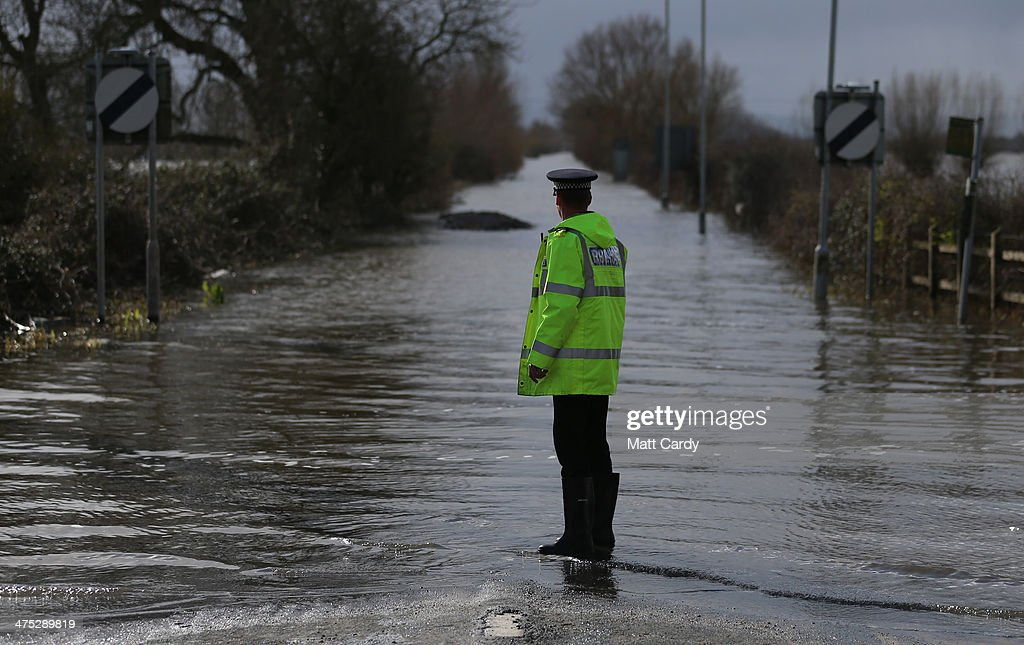A police officer looks at flood water at Burrowbridge on the Somerset Levels on February 27, 2014 in Somerset, England. According to the Met Office, England and Wales have experienced their wettest winter since records began in 1766, with parts of flood-hit southern England having experienced 83% more rain than average.