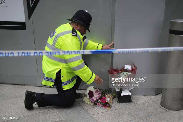 A police officer looks at floral tributes near the scene of last night's terrorist attack on June 4 2017 in London England Police continue to cordon...