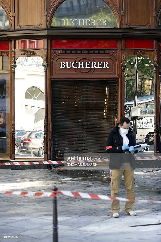 A police officer looks for evidence outside the jewellery store which was attacked by unidentified men with a motorized battering ram on May 5, 2014 in Paris' Opera district.