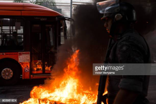 A police officer looks on after protesters linked to the social movements Front for Housing Struggle fired tires in protest against the Social...