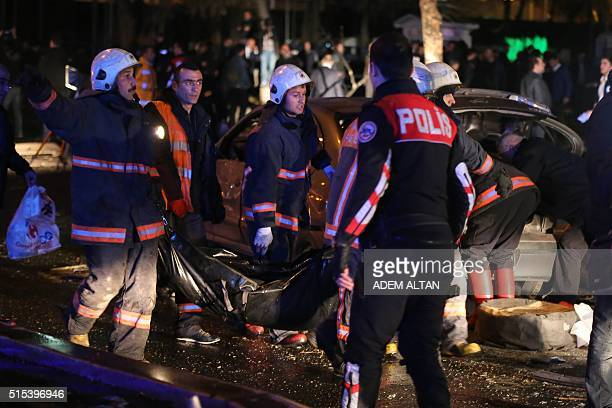 A police officer looks on as a body bag is carried at the scene of a blast in Ankara on March 13 2016 Several people were killed and many more...
