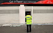 A police officer mans a cordon outside a restaurant on Prescot road in Liverpool northwest England on February 11 2015 Antiterror police arrested a...