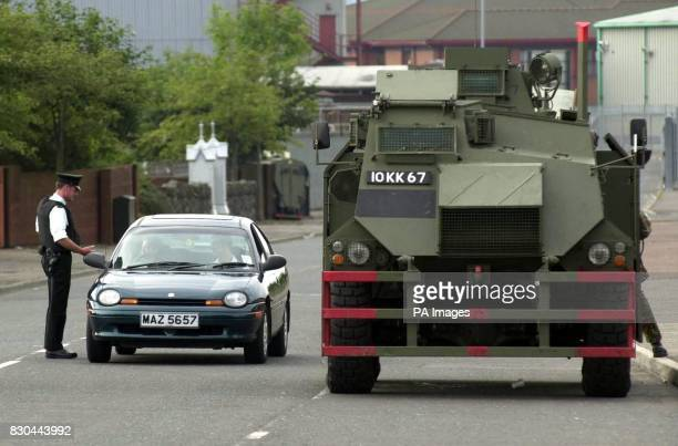 A police officer mans a vehicle checkpoint off the Shankill Road in Belfast after the British Government ordered troops back into the streets of...