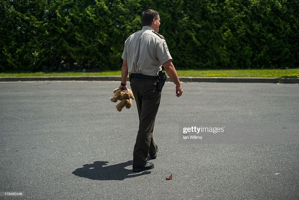 Police officer Marc Tessien carries a teddy bear, on July 14, 2013 in Lac-Megantic, Quebec, Canada. A train derailed and exploded into a massive fire that flattened dozens of buildings in the town's historic district, leaving 60 people dead or missing in the early morning hours of July 6.