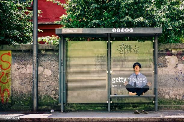 Officier de Police méditer sur la station de bus.