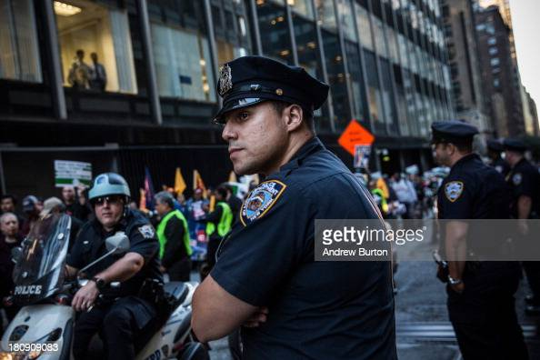 A police officer monitors Occupy Wall Street protesters as they march from the United Nations building to Bryant Park on September 17 2013 in New...