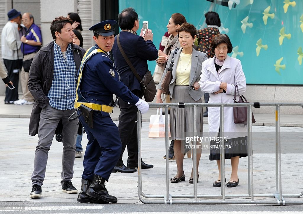 A police officer (C) moves a barricade to control the traffic in Ginza shopping district in Tokyo on April 23, 2014, hours before US President Barack Obama's visit. Obama will reportedly dine at a tiny Tokyo sushi restaurant, 'Sukiyabashi Jiro' a place with three coveted Michelin stars but only a handful of seats, ruled with an iron rod by its redoubtable 88-year-old owner, Jiro. Obama will come to Tokyo for a three-day visit from April 23 for and will have dinner with Japanese Prime Minister Shinzo Abe.