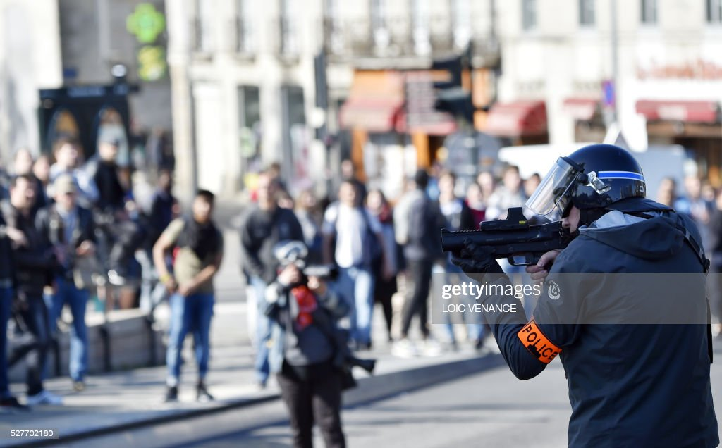 A police officer of the anti-criminality brigade (BAC) takes position during a protest against the government's planned labour law reforms in Nantes, western France, on May 3, 2016. High school pupils and workers protested against deeply unpopular labour reforms that have divided the Socialist government and raised hackles in a country accustomed to iron-clad job security. / AFP / LOIC