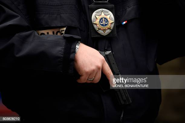 A police officer of the French national police stands armed near the Rue de la Goutte d'Or in the north of Paris on January 7 after police shot a man...