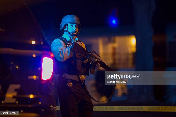 A police officer officer guards a police line as officers prepare to raid the home of one or more suspects of a mass shooting at the Inland Regional...