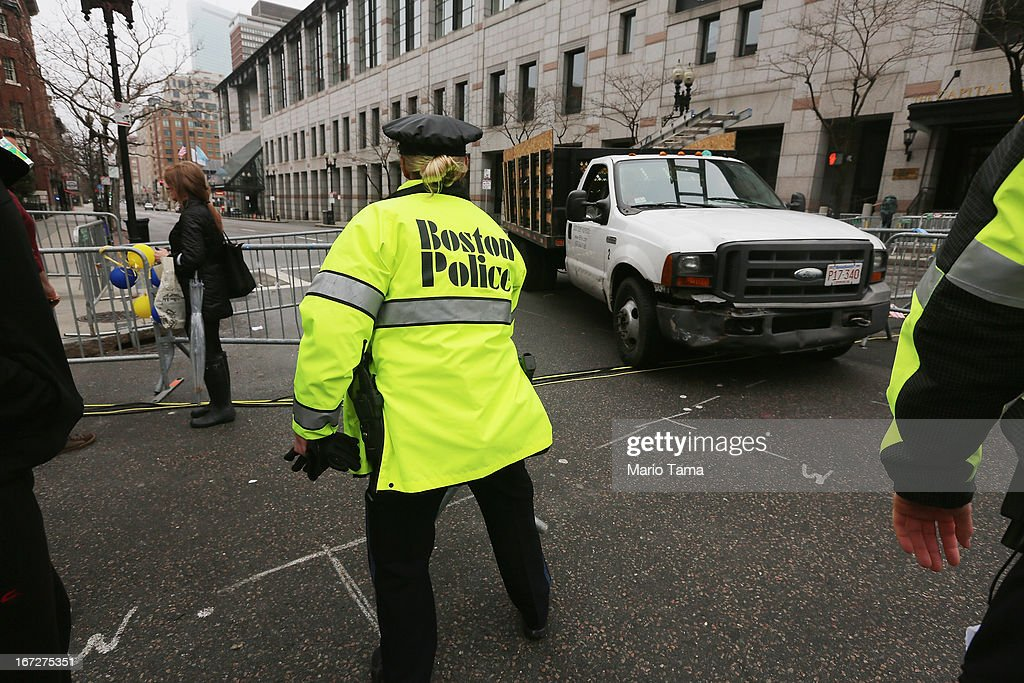 A police officer opens a barricade blocking a still closed section of Boylston Street for a passing vehicle near the site of the Boston Marathon bombings on April 23, 2013 in Boston, Massachusetts. Business owners and residents of the closed section were allowed to return to their properties today while under escort of city staff.