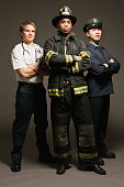 Police officer, paramedic and fireman, on black background, portrait