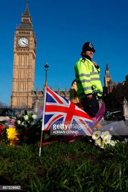 A police officer passes floral tributes to the victims of the March 22 terror attack in Parliament Square outside the Houses of Parliament in central...