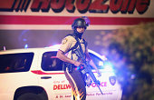 A police officer patrols a business district on August 13 2014 in Ferguson Missouri Ferguson is experiencing its fourth day of unrest after following...