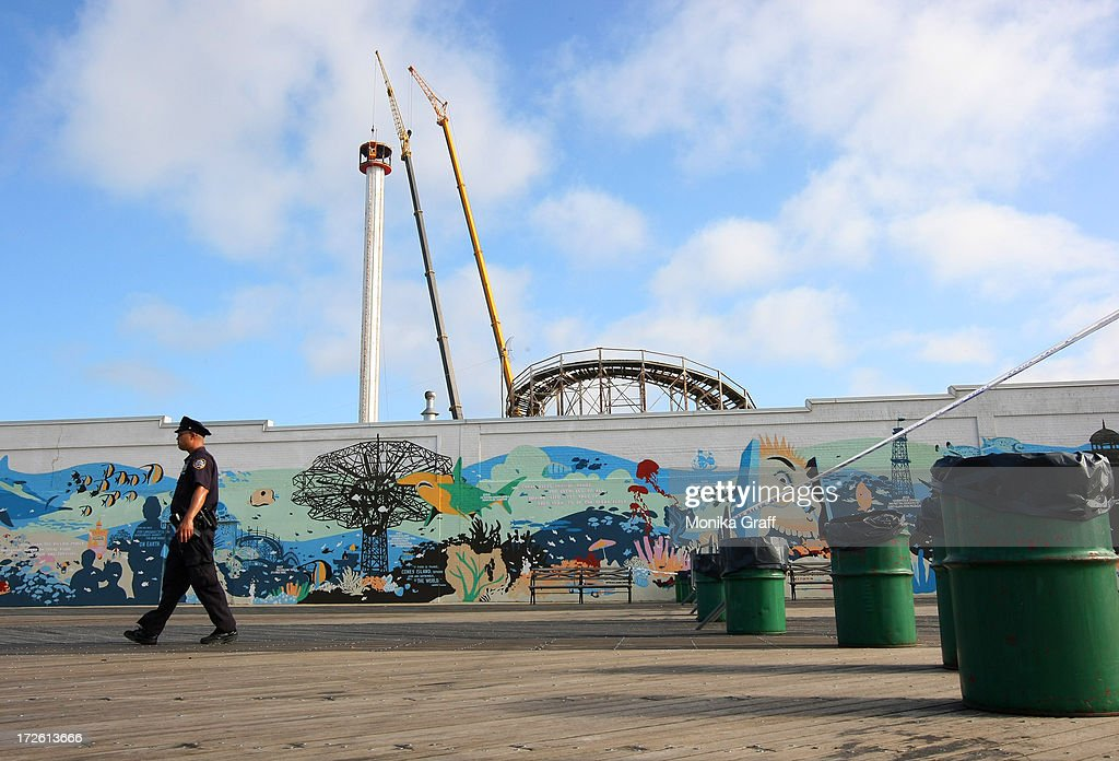 A police officer patrols a sections of the boardwalk which is closed off to the public as the Astrotower is disassembled in Coney Island on July 4, 2013 in the Brooklyn borough of New York City. Officials decided to close Luna Park and sections of the boardwalk while workers take down the amusement tower which was seen precariously swaying two days ago.