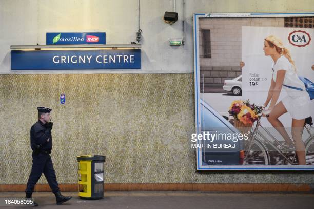 A Police officer patrols in and outside Grigny centre train station a Parisian suburb on March 19 where passengers of a RER D train were robbed with...