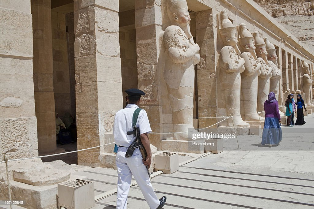 A police officer patrols in front of statues at the Temple of Hatshepsut in Luxor, Egypt, on Thursday, April 25, 2013. Egypt ranked last in terms of security and safety on the World Economic Forum's 2013 Travel and Tourism Competitiveness Index. Photographer: Shawn Baldwin/Bloomberg via Getty Images