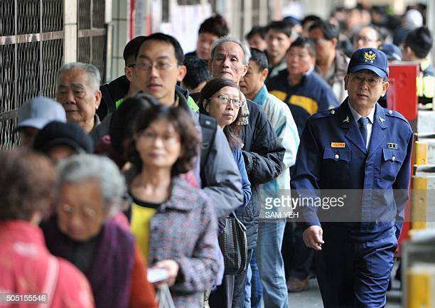 A police officer patrols outside a polling station as local residents line up to vote at the Xindian district in the New Taipei City on January 16...