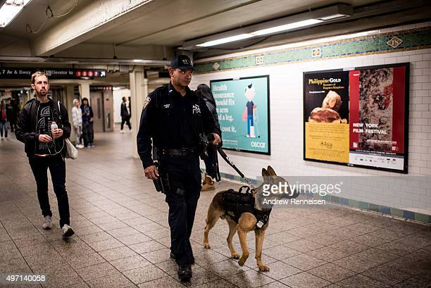 A police officer patrols the Times Square subway stop with his dog following a series of terrorist attacks in Paris on November 14 2015 in New York...